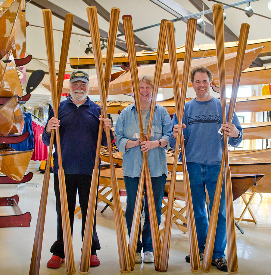 John Lockwood with Brita and Randy Isselin of Northpoint Paddles, posing with some freshly made paddles in the Pygmy Showroom.